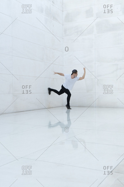 Casual man posing and dancing in white spacious room.