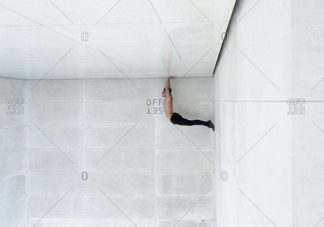 Upside down shot of strong shirtless man standing on hands in corner of tiled white room.