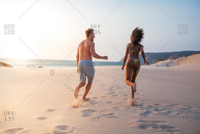 Happy couple running on tropical romantic beach