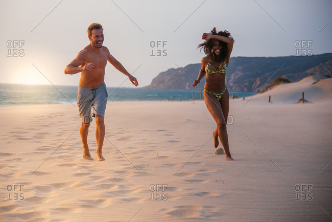 Happy couple running on tropical romantic beach