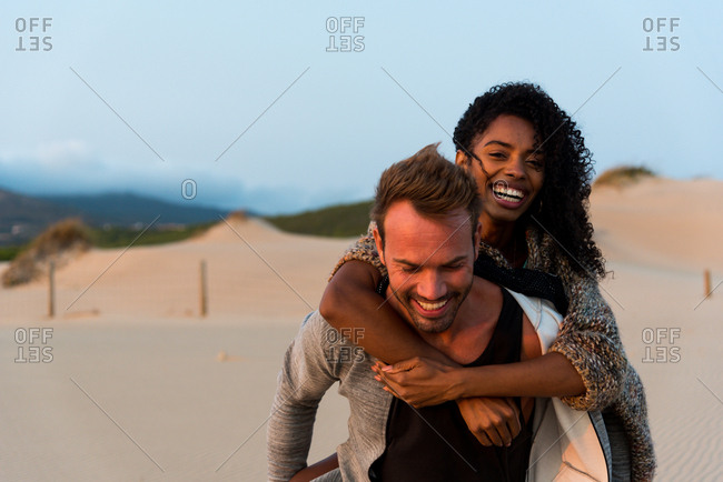 Laughing couple posing on beach
