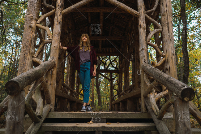 Young casual model standing in beautiful handicraft passage made of wood in park.