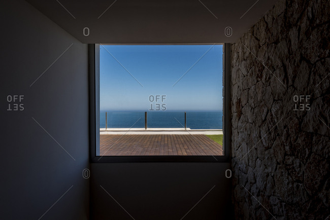 Inside shot of square window with landscape of terrace and ocean behind.