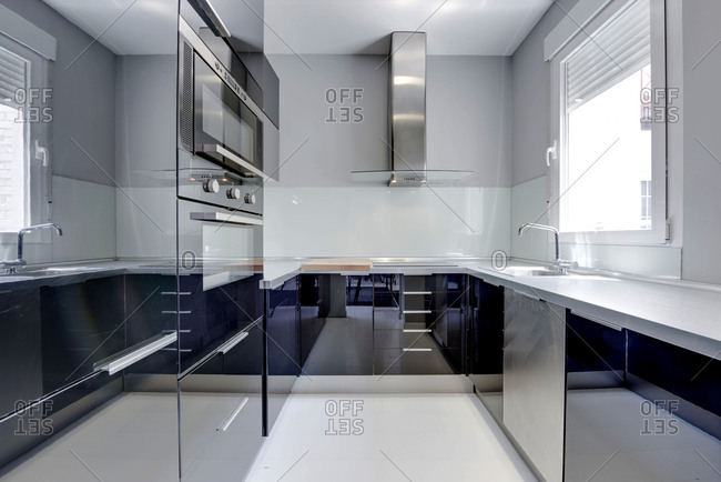 Inside view of kitchen design in modern style with plenty of shiny chrome surfaces.