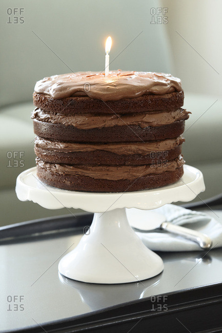 Layered Chocolate Birthday Cake with Lit Candle on Cake Stand on Coffee Table
