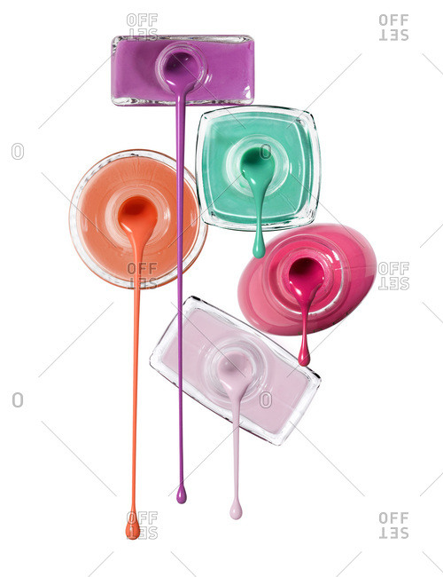 Close-up of Nail Polish Dripping from Bottles on White Background