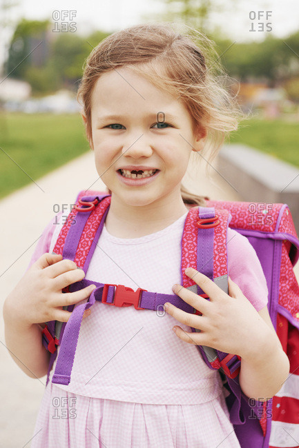 Portrait of 5 year old schoolgirl with pink and purple school bag, smiling and looking at camera showing her front teeth missing