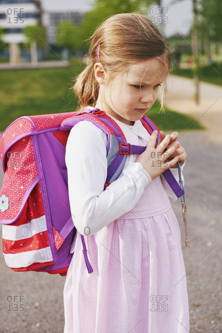 Portrait of 5 year old schoolgirl with her pink and purple school bag, day dreaming