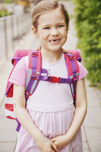 5 Year Old Schoolgirl with Pink School Bag Smiling with Missing Teeth