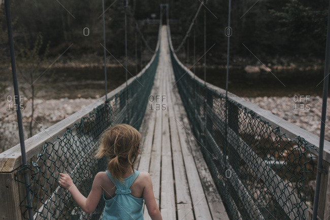 Girl standing at the end of a long suspension bridge