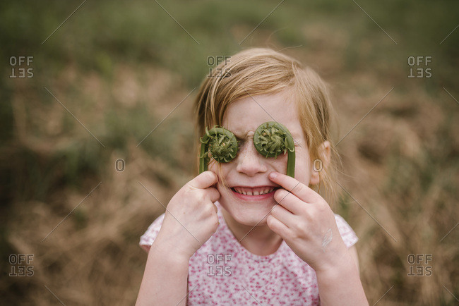 Portrait of a smiling girl holding fiddlehead ferns in front of her eyes