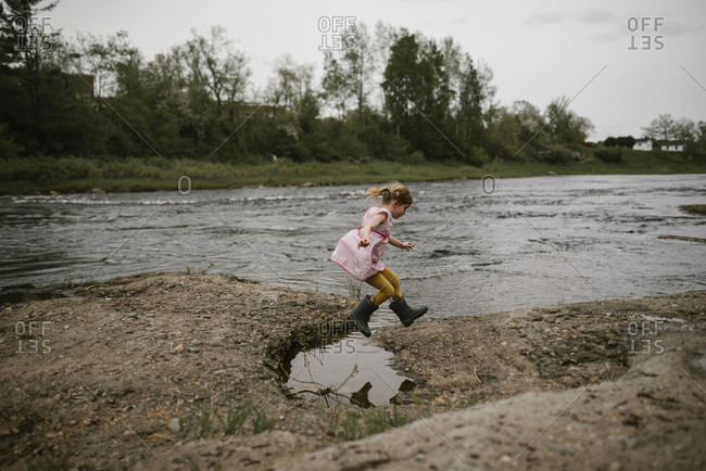 Girl leaping over a pool of water next to river
