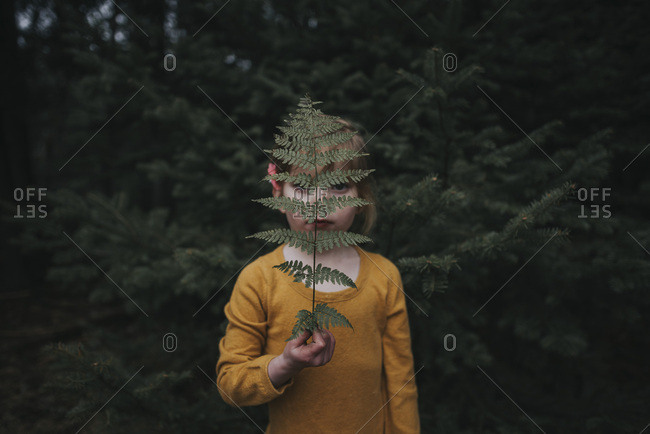 Girl holding fern frond in front of face