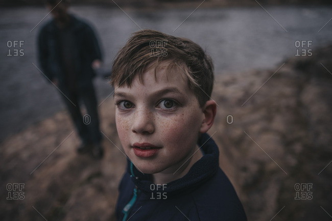 Portrait of a boy with brown hair and freckles standing outside