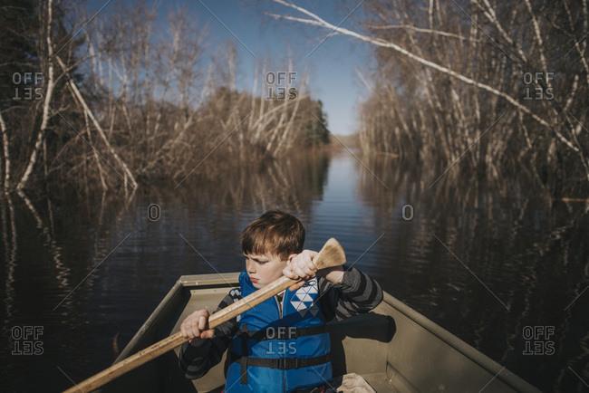 Boy in row boat using oar