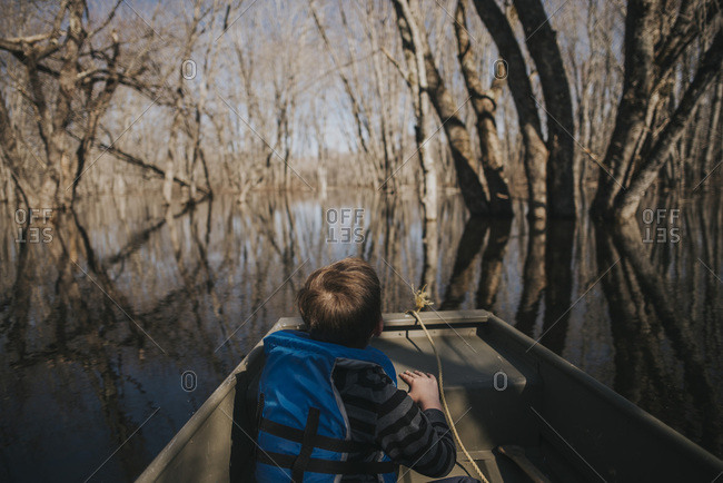 Boy in rowboat looking at trees in natural wetlands area