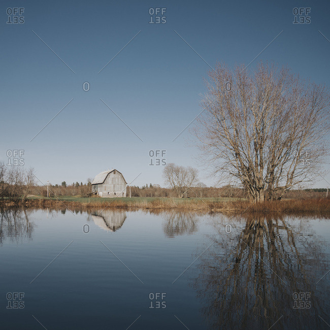 Barn and bare trees reflected in lake