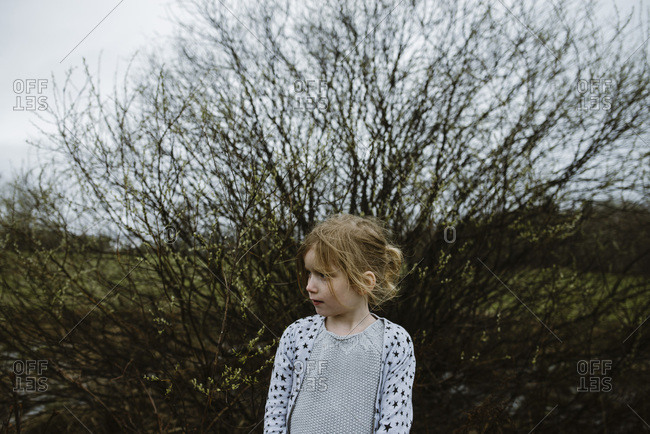 Portrait of a girl looking to side standing in front of tree