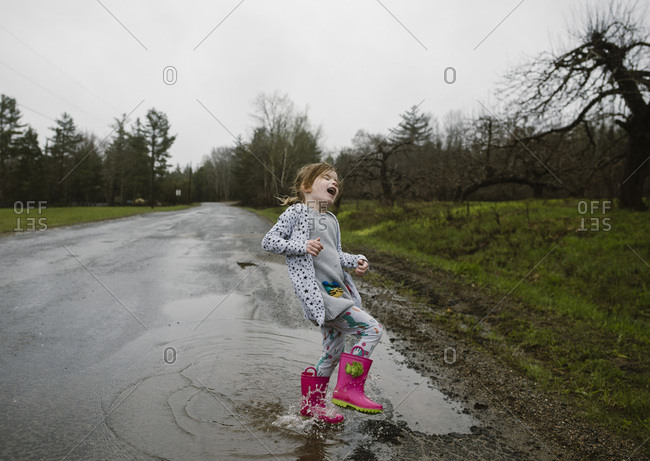 Girl wearing rubber boots splashing in puddle on country road