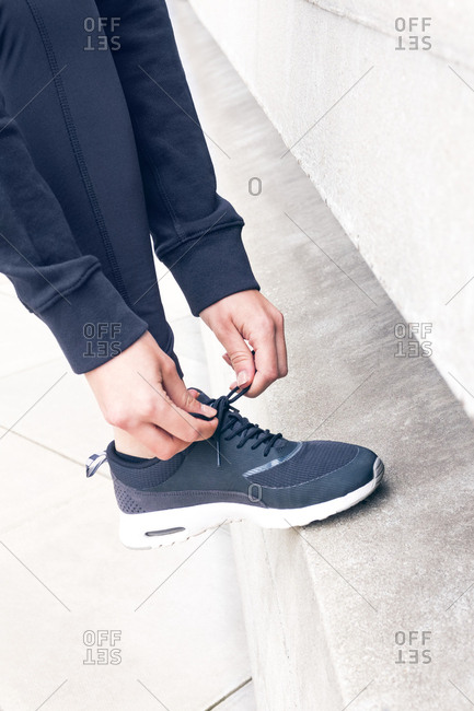 Woman tying trainers with foot on step