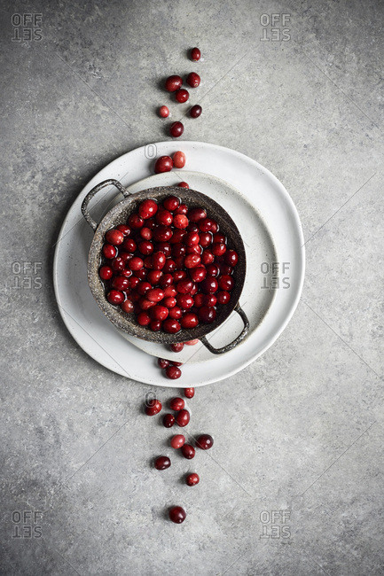 Metal bowl filled with cranberries on stack of plates with more cranberries cutting through the frame vertically, starkly contrasting with the cool tones of the textured, gray metal beneath.
