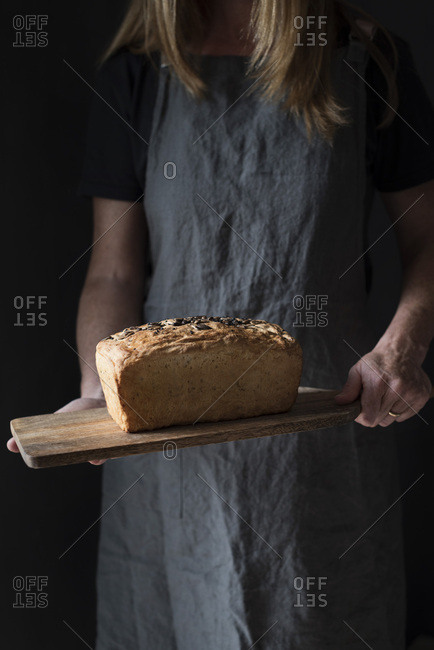 Woman holding a fresh baked loaf of bread