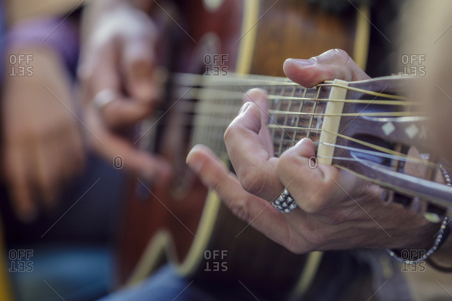 Detail of man hands while playing guitar