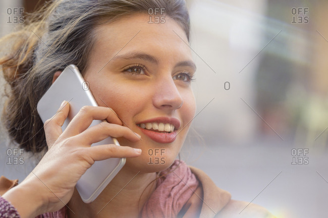 Portrait of smiling caucasian woman talking using smartphone