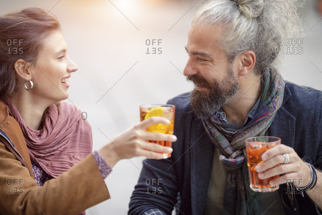 Man and woman toasting with cocktail during aperitif at italian cafe