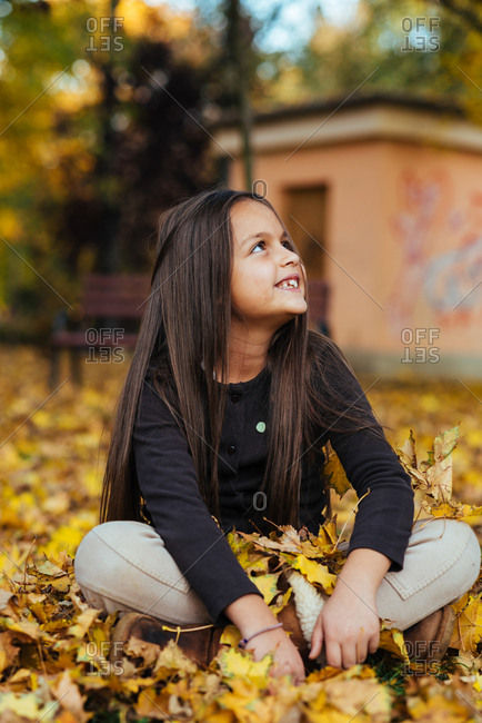 Cute eight year old girl sitting on the ground on a pile of yellow autumn leaves smiling