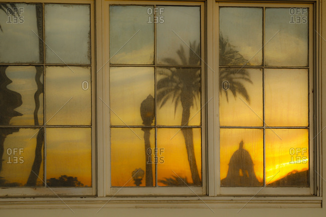 Reflection of palm tree and sunset in window at train station in Southern California
