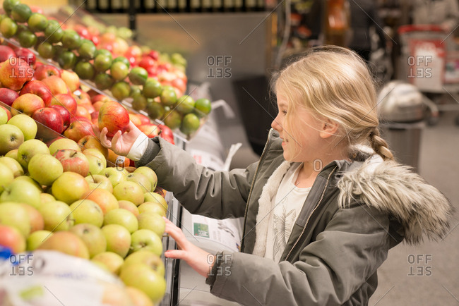 Little girl picking up apple in a grocery store