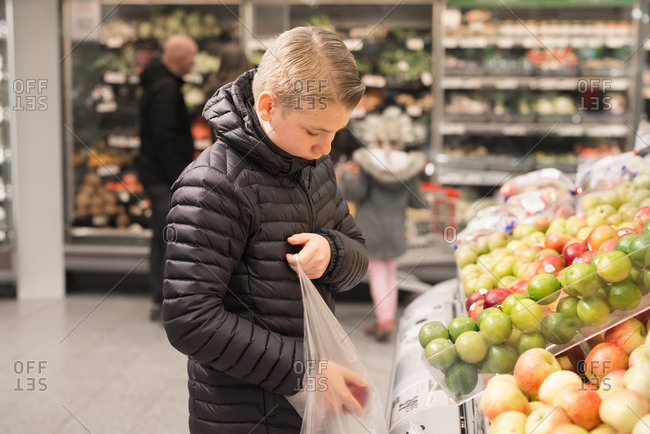Young boy selecting apples in a grocery store