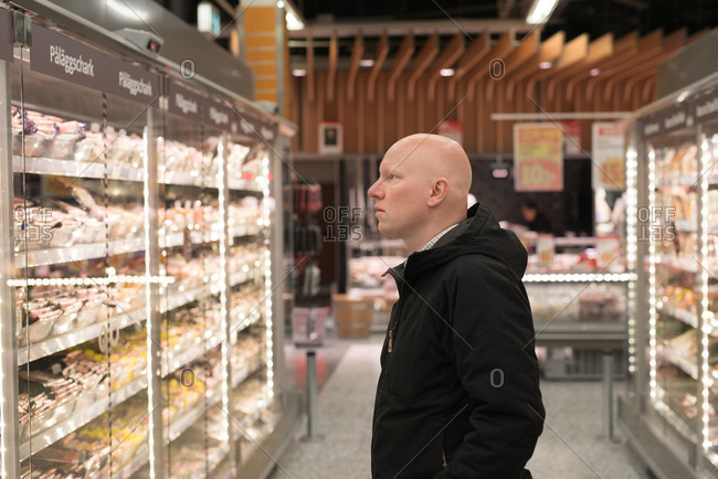 Man looking at meet refrigerator in a grocery store