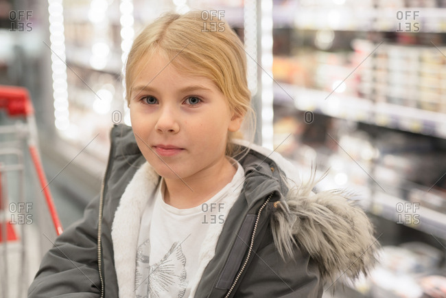 Portrait of a young blonde girl in a grocery store