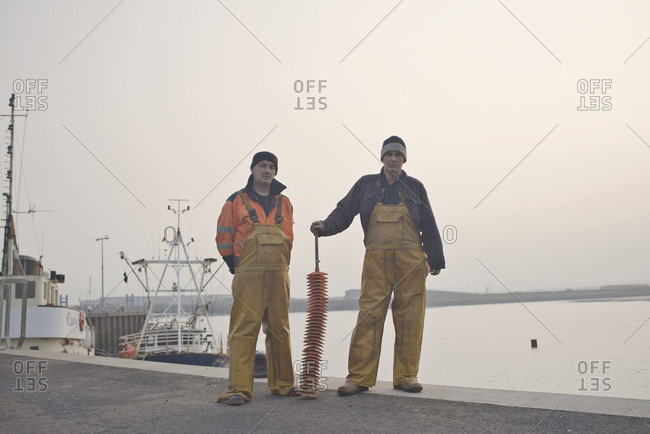 Portrait of two fishermen standing on the coast of Scotland