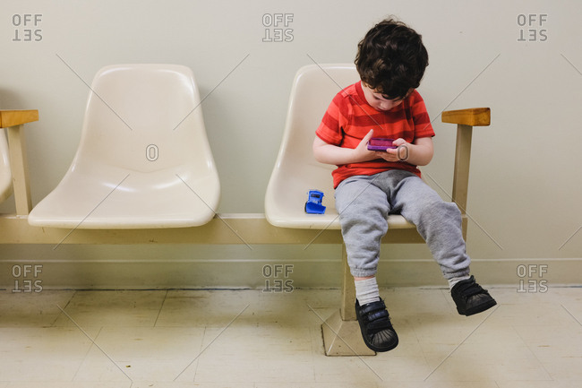 Little boy playing on Smartphone in a waiting room