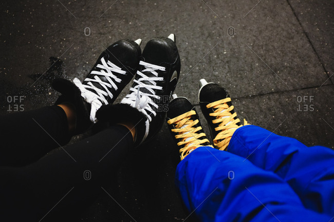 View of two people wearing ice skates at an indoor ice rink