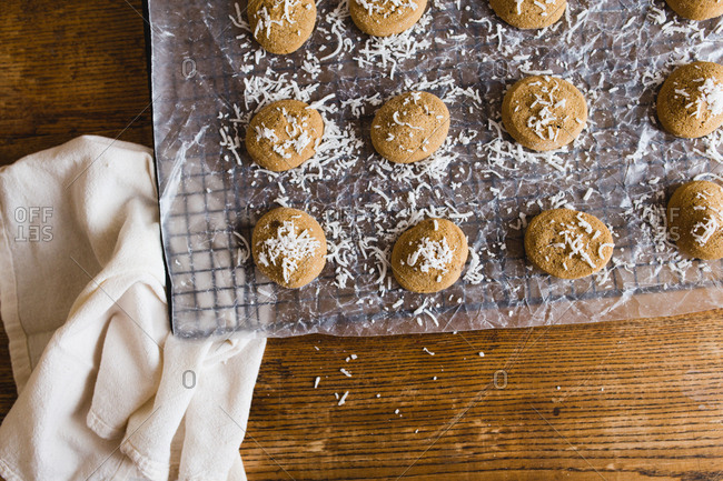 Cookies topped with coconut on parchment paper