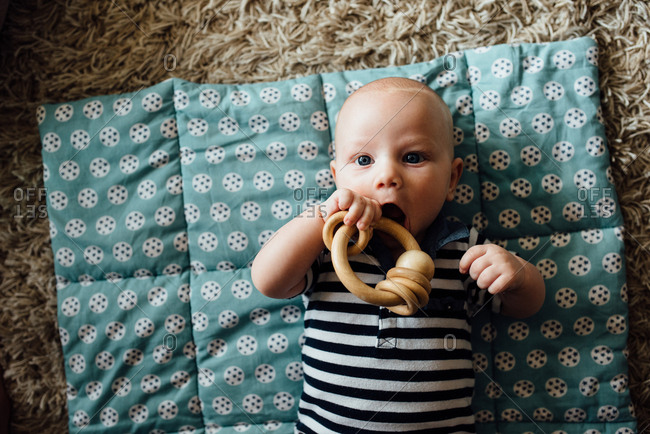 Teething baby boy chewing on wooden toy