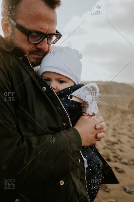 Father holding baby outdoors in a baby carrier
