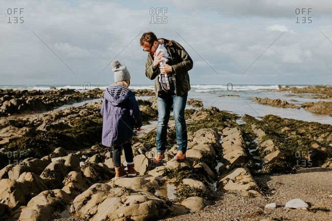 Father walking on a rocky beach with his two small children