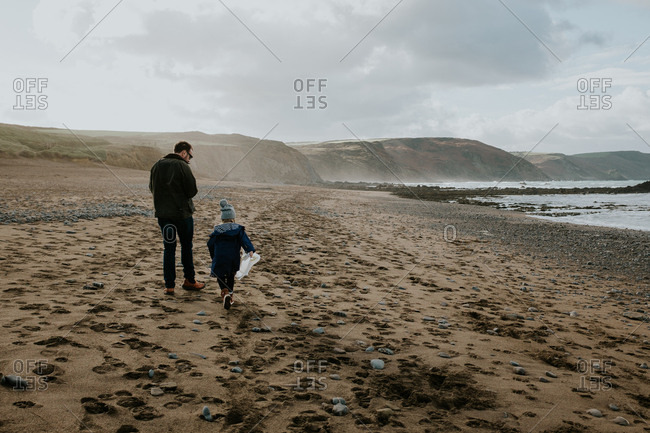 Father walking on a rocky beach with his daughter