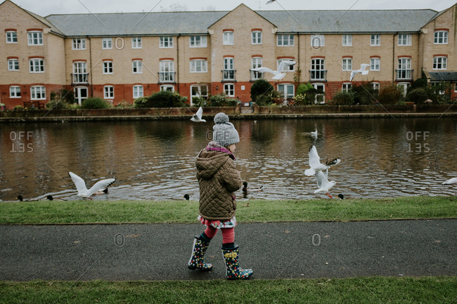 Little girl walking on bath beside river with seagulls