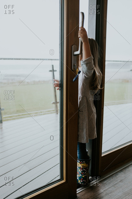 Little girl looking out between open sliding doors