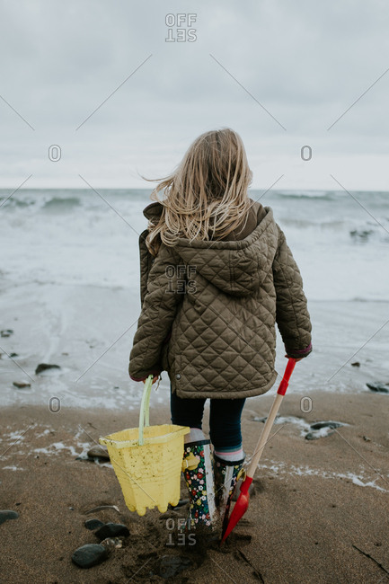 Young girl carrying bucket and shovel on a beach