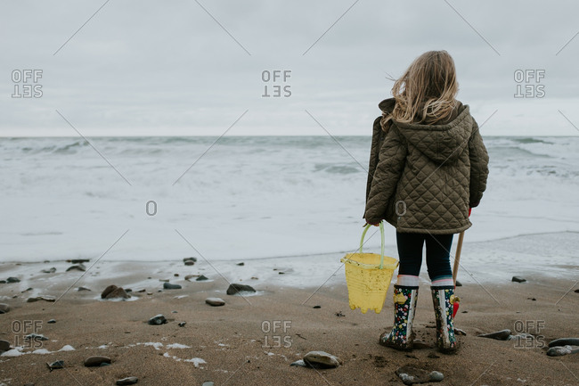 Blonde girl carrying bucket and shovel on a beach