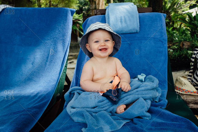 Happy baby sitting on lounge chair with blue towel