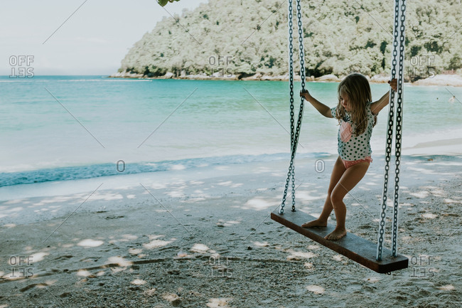Young girl swinging on a beach swing
