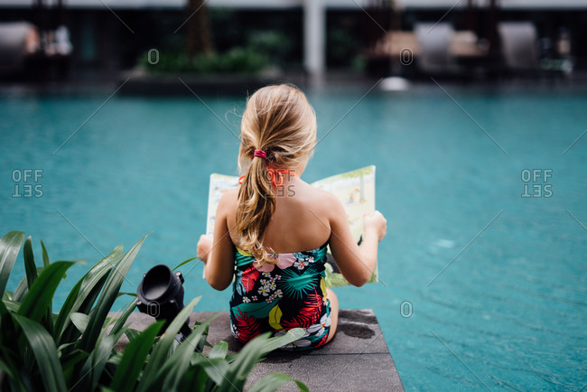 Young girl reading a book beside a pool